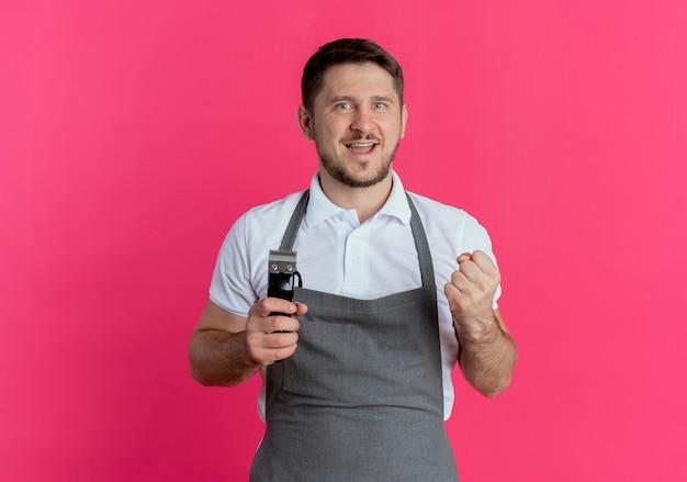 ピンクの背景の上に立って幸せで興奮した拳を握りしめるひげトリマーを保持しているエプロンの理髪店の男