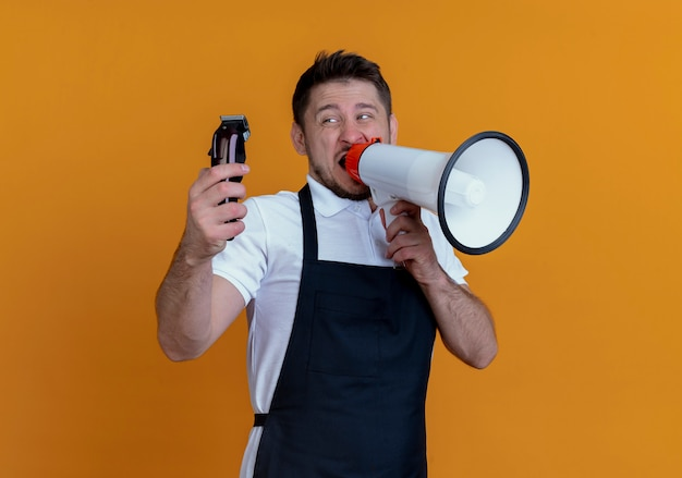 오렌지 벽 위에 서있는 확성기에 외치는 수염 트리머를 들고 앞치마에 이발사 남자