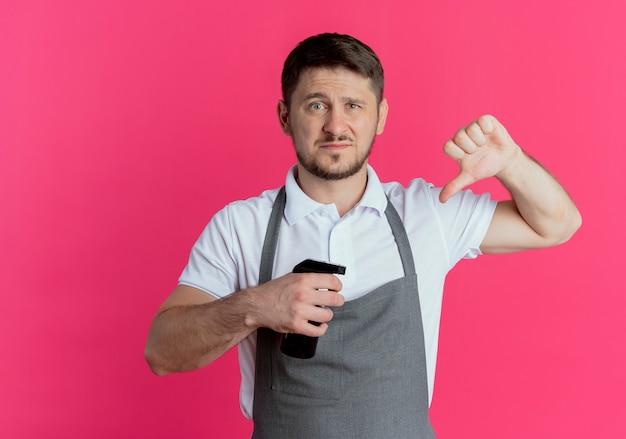 분홍색 배경 위에 서서 불쾌 해하는 아래로 엄지 손가락을 보여주는 수염 트리머를 들고 앞치마에 이발사 남자