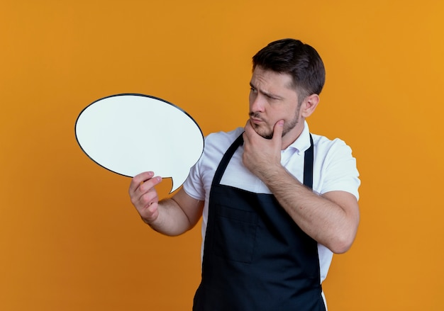Парикмахер в фартуке держит пустой речевой знак пузыря, глядя на него, думая, стоя на оранжевом фоне