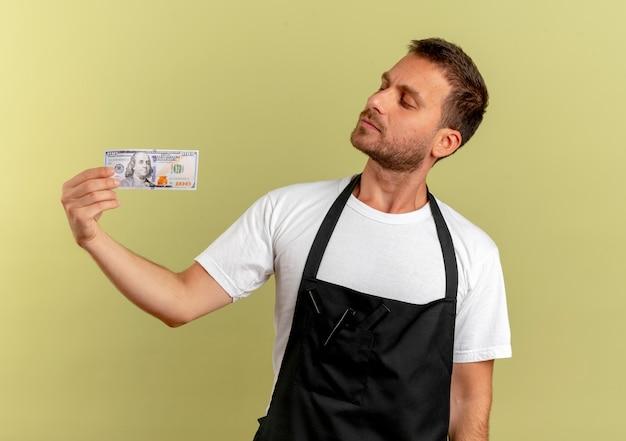 가벼운 벽 위에 서 심각한 얼굴로 찾고 현금을 들고 앞치마에 이발사 남자