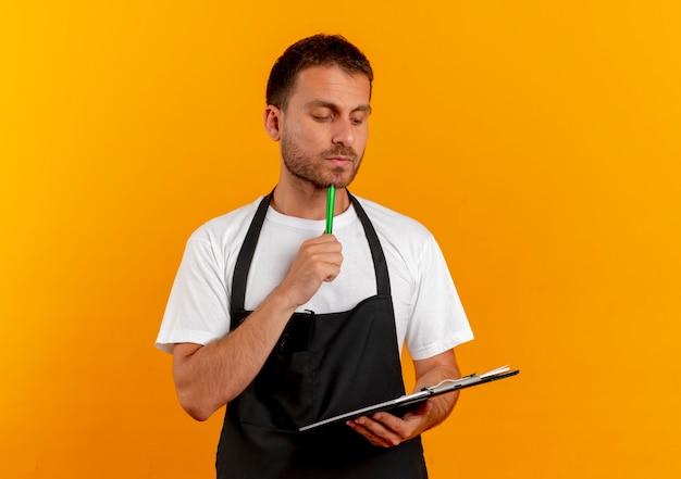 클립 보드와 펜을 들고 앞치마에 이발사 남자가 오렌지 벽 위에 서있는 잠겨있는 표정으로 찾고