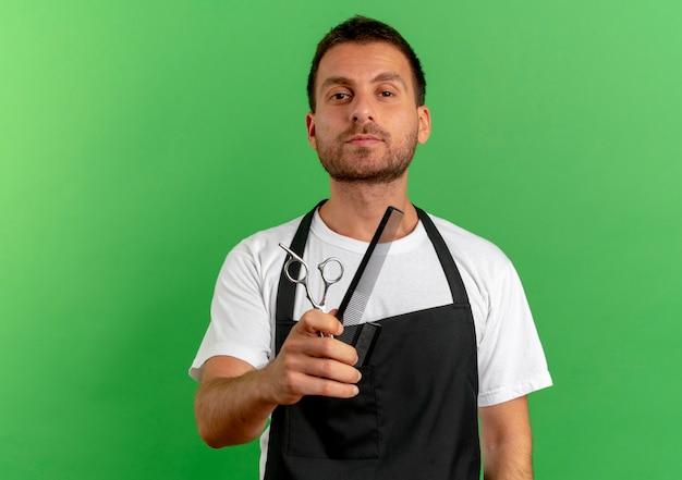 Парикмахер в фартуке держит расческу и ножницы, уверенно глядя вперед, стоит над зеленой стеной