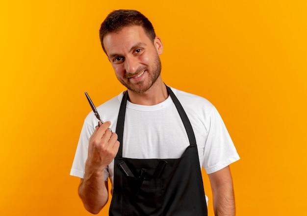 Парикмахер в фартуке, держащий гребень, глядя вперед, уверенно улыбаясь, стоит над оранжевой стеной