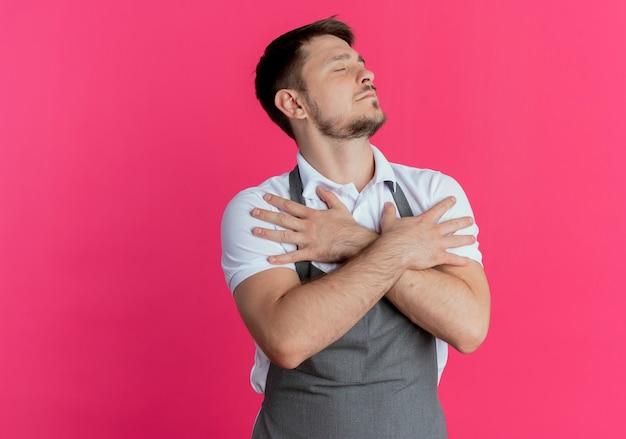 ピンクの壁の上に立っている目を閉じて感謝している彼の胸に交差した腕を保持しているエプロンの床屋の男