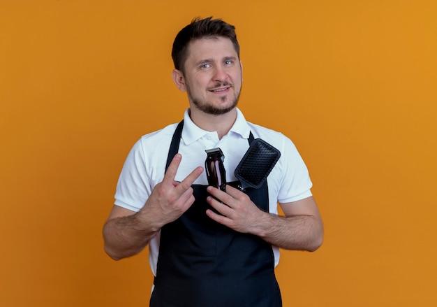 オレンジ色の壁の上に立っている2番目を示す顔に笑顔でヘアブラシとひげトリマーを保持しているエプロンの床屋の男