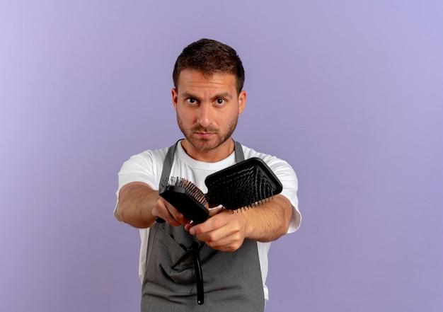 紫色の壁の上に立っている深刻な顔で正面を向いているヘアブラシを保持しているエプロンの床屋の男
