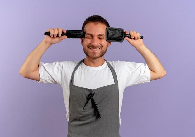 紫色の壁の上に立っている目を閉じて元気に笑っているヘアブラシを保持しているエプロンの理髪店の男