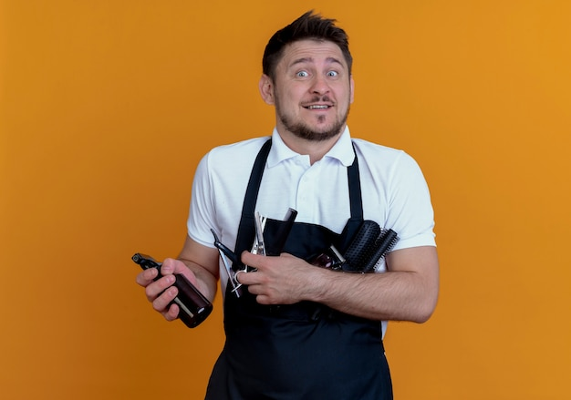 머리 브러쉬, 스프레이 및 가위를 들고 앞치마에 이발사 남자 오렌지 벽 위에 서 혼란 스 러 워 미소