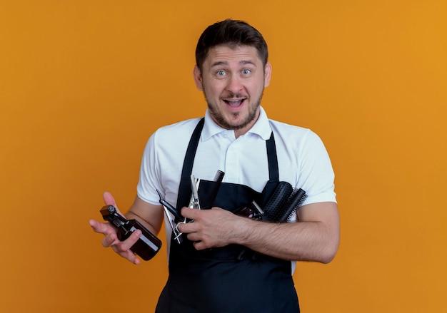 Парикмахер в фартуке с щетками, спреем и ножницами, улыбаясь, стоит над оранжевой стеной