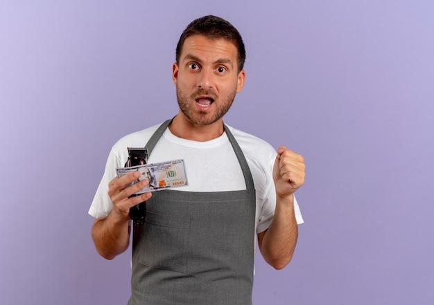 紫色の壁の上に立っている髪の切断機と現金幸せで興奮した握りこぶしを保持しているエプロンの床屋の男