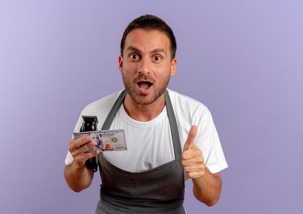 髪の切断機と現金を保持しているエプロンの床屋の男は、紫色の壁の上に立って親指を見せて幸せで興奮しています