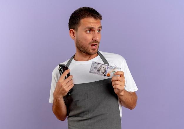 Парикмахер в фартуке держит машинку для стрижки и деньги, смущенно глядя в сторону, стоя у фиолетовой стены