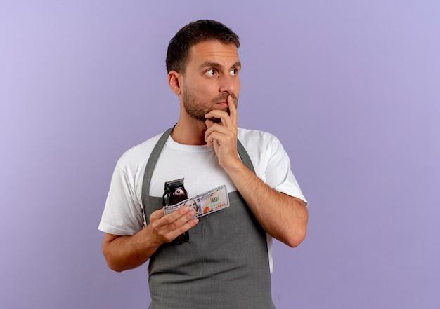 Парикмахер в фартуке держит машину для стрижки и деньги, глядя в сторону, думая, стоя над фиолетовой стеной