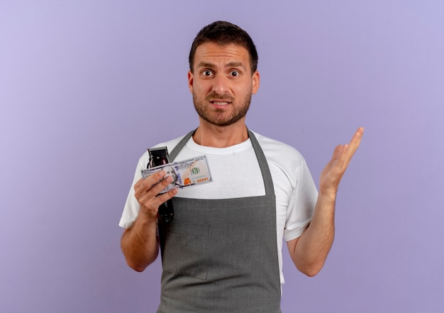Парикмахер в фартуке, держащий машинку для стрижки волос и деньги, смущенный взглядом вперед, стоящий над фиолетовой стеной