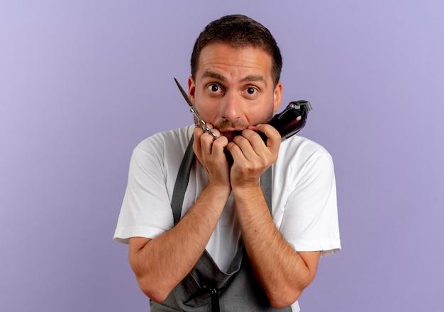 髪の切断機とはさみを持っているエプロンの床屋の男は、紫色の壁の上に立っているストレスと神経質な噛む爪を強調しました