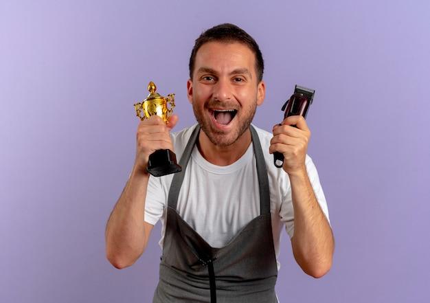 Парикмахер в фартуке, держащий машинку для стрижки и трофей, счастливые и взволнованные улыбающиеся, весело стоящие над фиолетовой стеной