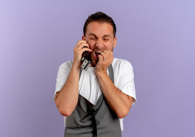 머리 절단 기계를 들고 앞치마에 이발사 남자는 보라색 벽 위에 서서 공황 상태에서 스트레스와 긴장 소리