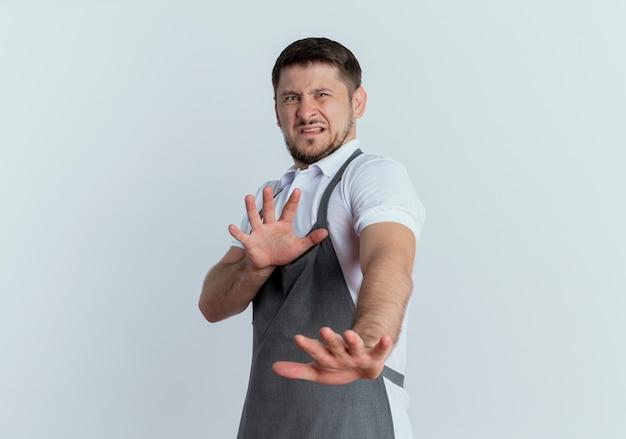 앞치마에 이발사 남자가 흰색 배경 위에 서있는 혐오스러운 표정으로 방어 제스처를 만드는 손을 잡고