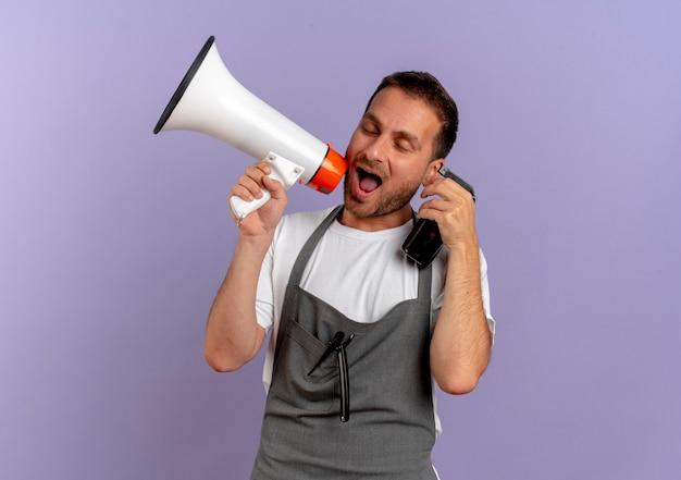 Парикмахер в фартуке держит мегафон, кричит сквозь него, держа машину для стрижки волос возле лица, стоящего над фиолетовой стеной