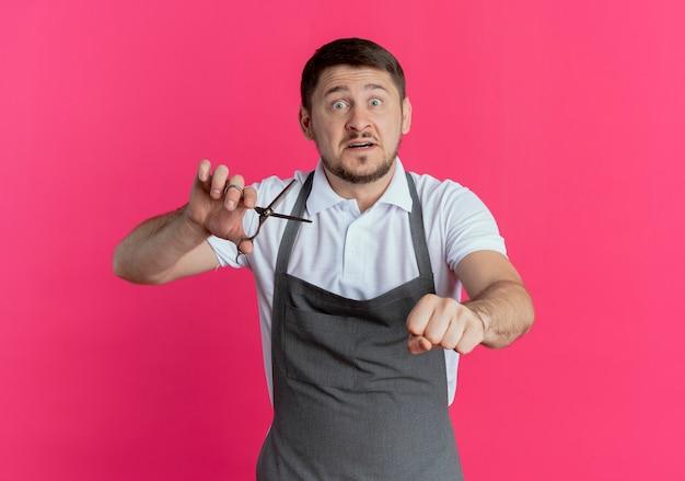 ピンクの背景の上に立って心配そうに見える拳を握り締めはさみを持っているエプロンの理髪店
