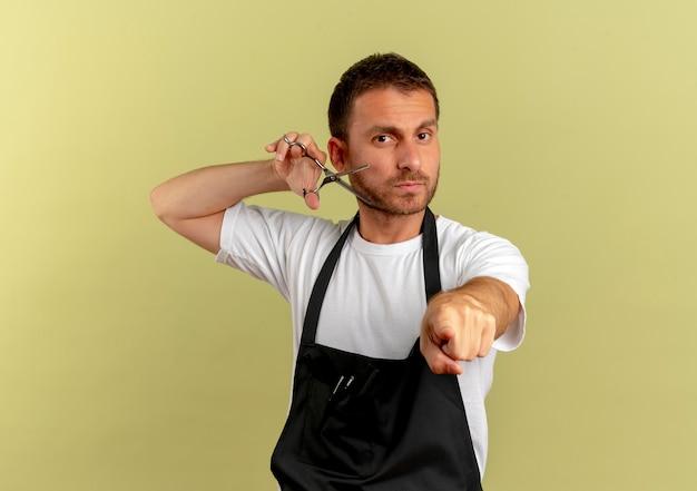 가벼운 벽 위에 서있는 자신감있는 표정으로 앞치마 검지 손가락으로 가리키는 가위를 들고 앞치마에 이발사 남자