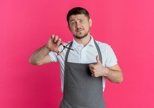 ピンクの壁の上に立っている顔に笑顔で親指を示すはさみを保持しているエプロンの床屋の男