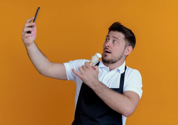 オレンジ色の背景の上に立っているスマートフォンを使用して自分撮りを取っている彼の顔にシェービングフォームを置くシェービングブラシを保持しているエプロンの理髪店の男