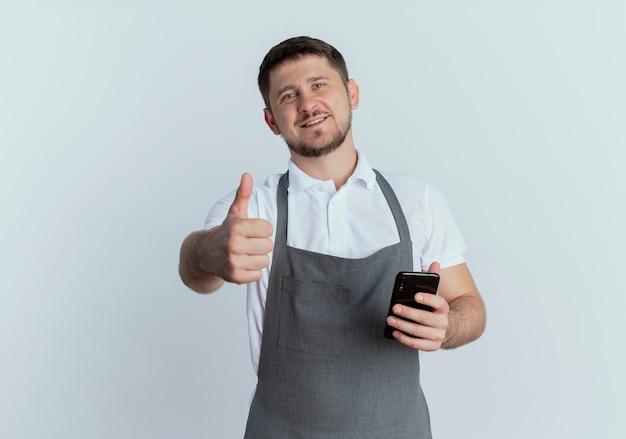 白い壁の上に立っている幸せそうな顔で笑顔で親指を示すスマートフォンを保持しているエプロンの理髪店の男