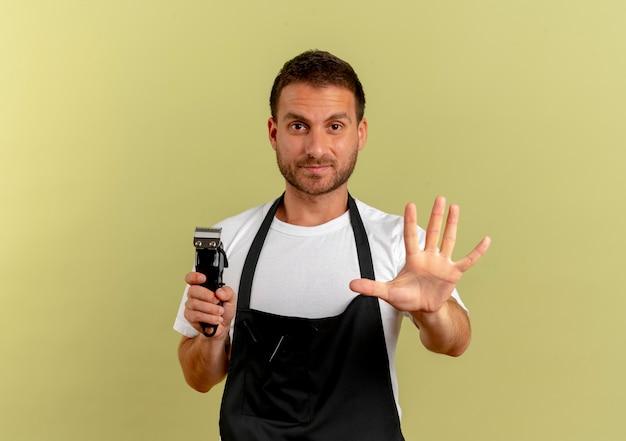 Парикмахер в фартуке держит триммер, делая стоп-сигнал с открытой рукой, глядя вперед с серьезным лицом, стоящим над светлой стеной