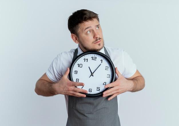 白い壁の上に立って困惑して脇を見て壁時計を保持しているエプロンの床屋の男