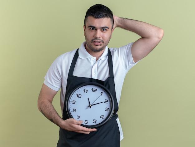 緑の背景の上に立っている彼の頭の上の手と混同されたカメラを見て壁時計を保持しているエプロンの理髪店の男