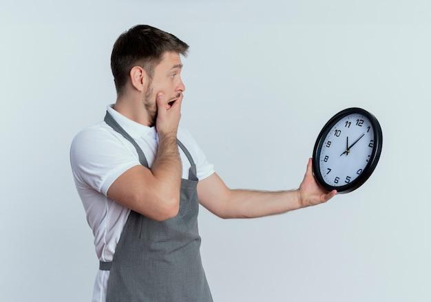 それを見て混乱し、白い背景の上に立って驚いた壁時計を保持しているエプロンの床屋の男