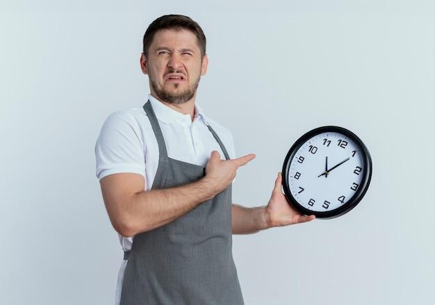 白い壁の上に立って混乱して非常に心配そうに見える壁時計を指で指しているエプロンの床屋の男