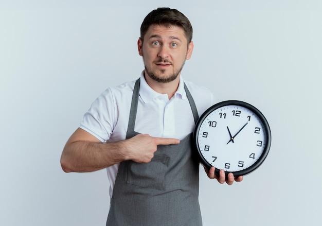 白い背景の上に立って驚いて見える壁時計を指で指しているエプロンの床屋の男