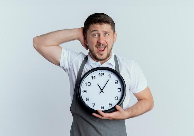 壁時計を保持しているエプロンの床屋の男は、白い壁の上に立って困惑し、混乱しています