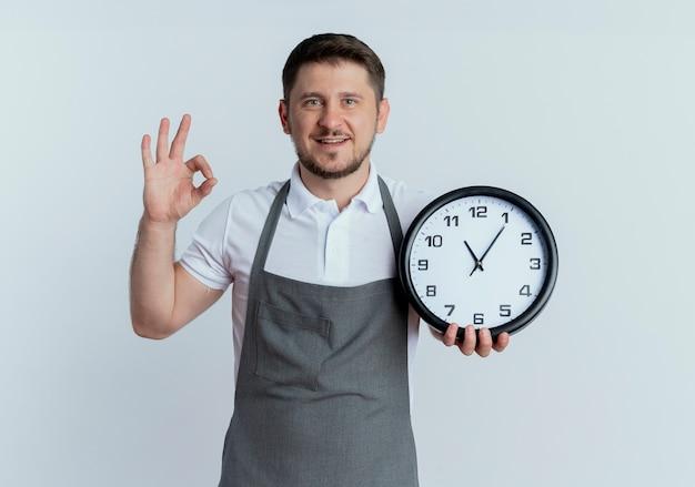 白い背景の上に立って笑顔でokサインを示す壁時計を保持しているエプロンの理髪店の男