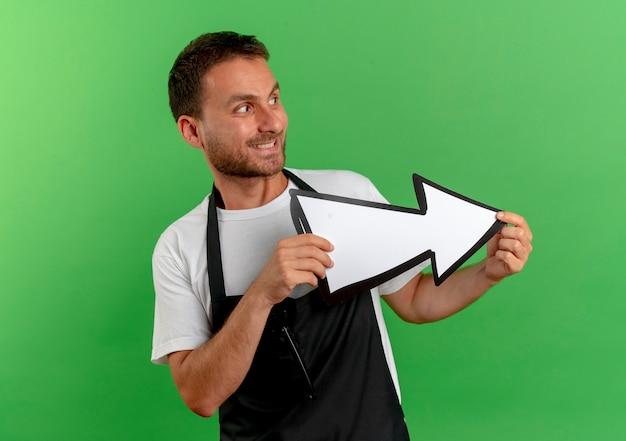 녹색 벽 위에 서있는 얼굴에 미소로 옆으로 찾고 흰색 화살표를 들고 앞치마에 이발사 남자
