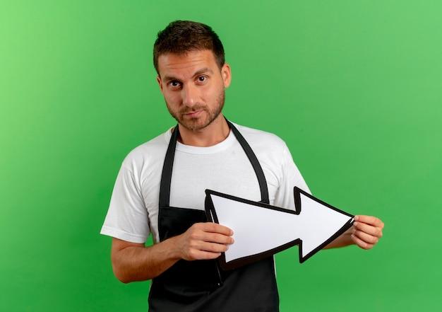 녹색 벽 위에 서 심각한 얼굴로 정면을 찾고 흰색 화살표를 들고 앞치마에 이발사 남자