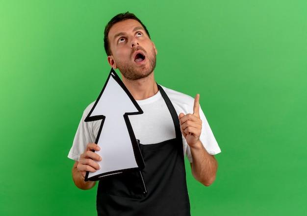 녹색 벽 위에 서있는 손가락으로 가리키는 흰색 화살표를 들고 앞치마에 이발사 남자