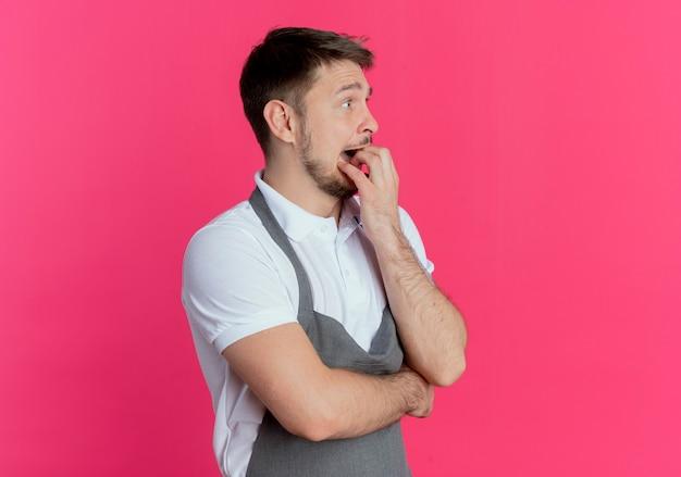 ピンクの壁の上に立っているストレスと神経質な噛む爪を脇に見ているエプロンの床屋の男