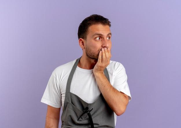 보라색 벽 위에 서있는 손으로 입을 덮고 스트레스를 받고 긴장된 앞치마를 입은 이발사 남자