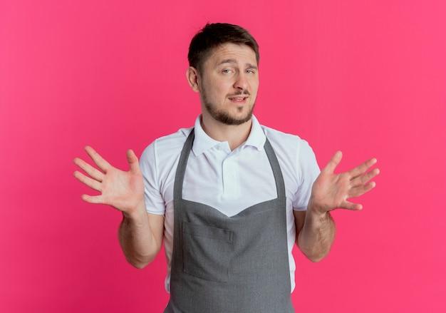 カメラを見ているエプロンの床屋の男は、ピンクの背景の上に立っている側に腕を広げて微笑んで混乱しました