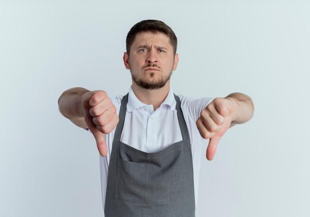 Парикмахер в фартуке смотрит в камеру недовольно, показывая большие пальцы вниз, стоя на белом фоне