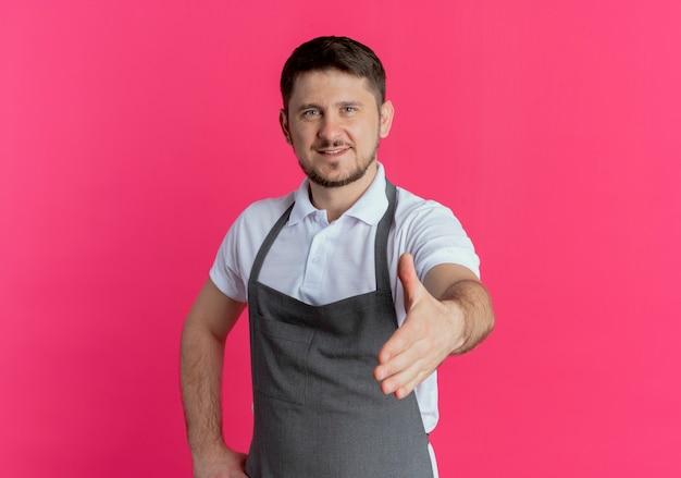 분홍색 배경 위에 친절한 서 미소 손 인사를 제공하는 카메라를보고 앞치마에 이발사 남자