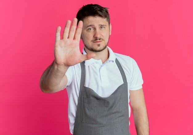 Парикмахер в фартуке смотрит в камеру с серьезным лицом, делая знак остановки с рукой, стоящей на розовом фоне
