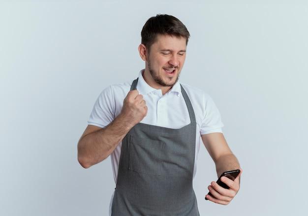 白い背景の上に立って幸せで興奮している彼のスマートフォンの握りこぶしの画面を見ているエプロンの理髪店の男