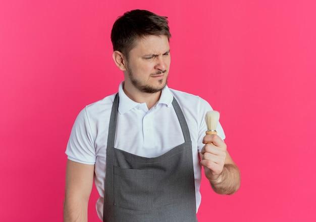 ピンクの背景の上に立っている深刻な顔で彼の手でシェービングブラシを見ているエプロンの理髪店の男