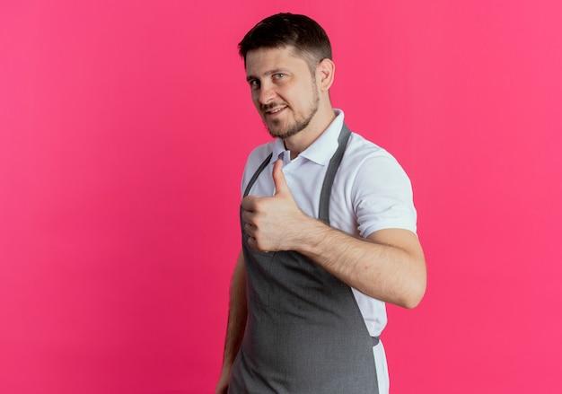ピンクの背景の上に立って親指を見せて自信を持って見えるエプロンの理髪店の男