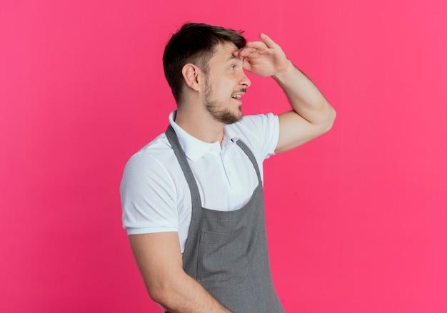 ピンクの壁の上に立っている何かを見るために頭上に手を渡して遠くを見ているエプロンの床屋の男